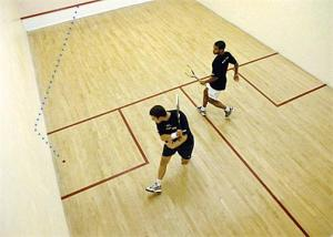"""A left boast, where a shot is taken off the left side-wall. Observe the other player watching his opponent as he takes the shot while moving into the """"T"""". Also observe that the player taking the shot is already in position with both his shot selection and footwork in place."""